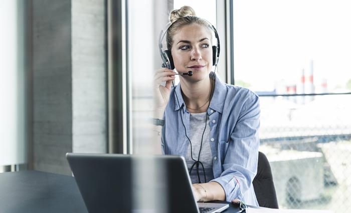 Donna con auricolare seduta davanti al portatile